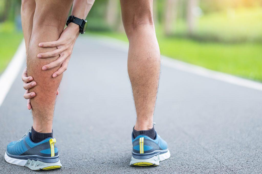 Homem segurando a perna inchada após corrida
